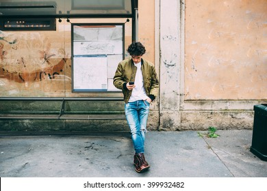 Young handsome caucasian man leaning on a bus stop holding a smart phone looking down and tapping the screen - technology, social network, communication concept