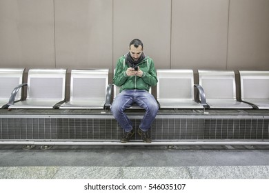 Young handsome caucasian man leaning on a bus metro underground stop holding a smart phone looking down and tapping the screen - technology, social network, communication concept
