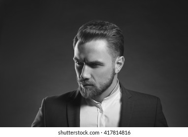 Young handsome caucasian man with perfect hairstyle wearing suit. Studio portrait on gradient black to grey background. Black and white