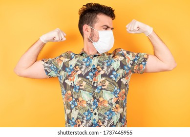Young handsome caucasian man with short hair wearing hawaiian shirt with medical mask and gloves  showing arms muscles smiling proud. Fitness concept.