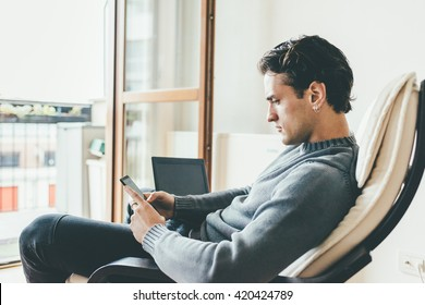 Young handsome caucasian man sitting on the sofa in his house using smart phone hand hold and notebook, looking down tapping the screen - business, technology, multitasking concept