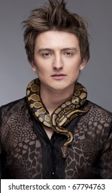Young, handsome caucasian man with snake around his neck; grey background, a lot of copyspace available
