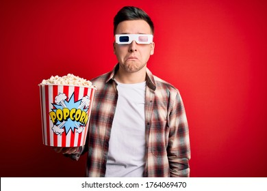 Young handsome caucasian man wearing 3d movie glasses and eating popcorn depressed and worry for distress, crying angry and afraid. Sad expression.