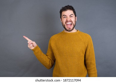 Young handsome Caucasian man wearing yellow sweater against gray wall points aside on copy blank space. People promotion and advertising concept