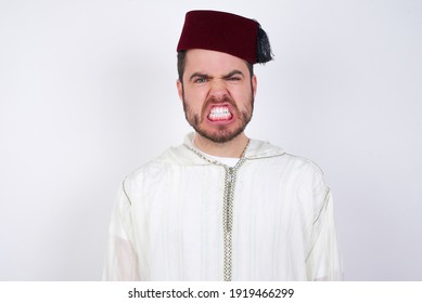 young handsome Caucasian man wearing Arab djellaba and Fez hat over white wall keeps teeth clenched, frowns face in dissatisfaction, irritated because of much duties.
