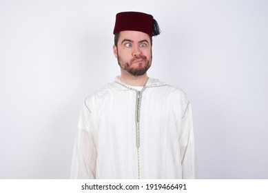 young handsome Caucasian man wearing Arab djellaba and Fez hat over white wall making grimace and crazy face, screaming out of control, funny lunatic expressing freedom and wild.