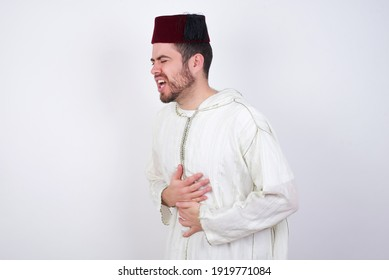young handsome Caucasian man wearing Arab djellaba and Fez hat over white wall with hand on stomach because nausea, painful disease feeling unwell. Ache concept.