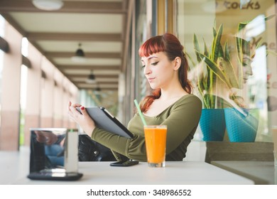 Young handsome caucasian redhead woman using tablet sitting in bar, with a juice and a smartphone on the table, looking downward, tapping the screen - technology, social network, multitasking concept