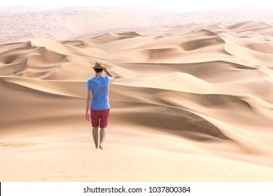 Young handsome caucasian tourist in shorts and straq hat hiking in Liwa desert dunes. Abu Dhabi, UAE.