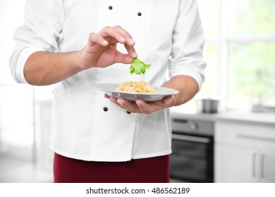 Young handsome chef cook preparing food in kitchen