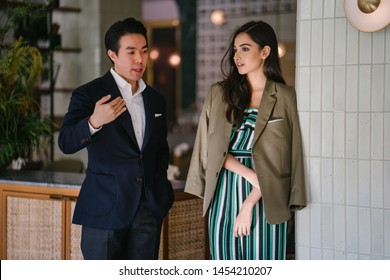 A young and handsome Chinese Asian man  in a suit stands with a beautiful, elegant and attractive Indian woman in a classy outfit in a well-decorated interior. They are talking to one another.