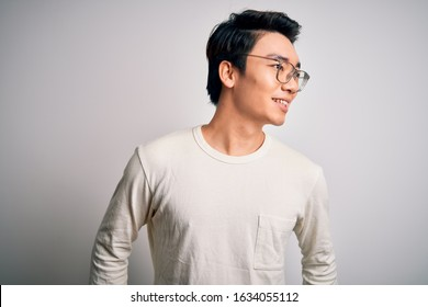 Young handsome chinese man wearing casual t-shirt and glasses over white background looking away to side with smile on face, natural expression. Laughing confident.