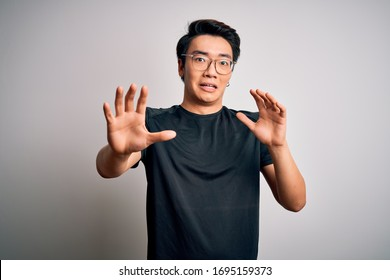 Young handsome chinese man wearing black t-shirt and glasses over white background afraid and terrified with fear expression stop gesture with hands, shouting in shock. Panic concept.