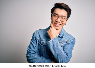 Young handsome chinese man wearing denim jacket and glasses over white background looking confident at the camera smiling with crossed arms and hand raised on chin. Thinking positive.