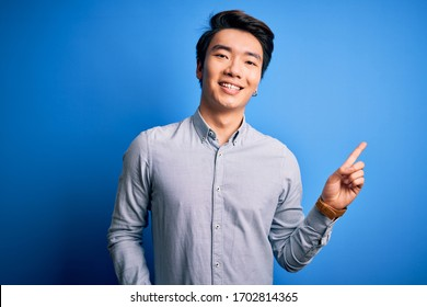 Young handsome chinese man wearing casual shirt standing over isolated blue background with a big smile on face, pointing with hand finger to the side looking at the camera.