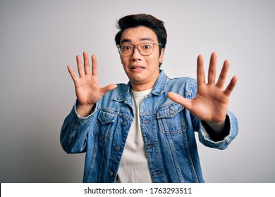 Young handsome chinese man wearing denim jacket and glasses over white background afraid and terrified with fear expression stop gesture with hands, shouting in shock. Panic concept.