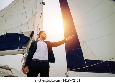 Young handsome and confident Caucasian businessman pointing finger forward on sailing yacht boat with ship mast in the background - leadership and visionary business concept