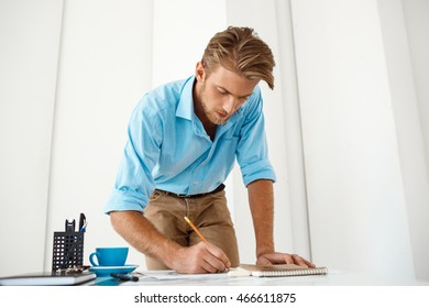 Young handsome confident pensive businessman working standing at table writing in notepad. White modern office interior background.