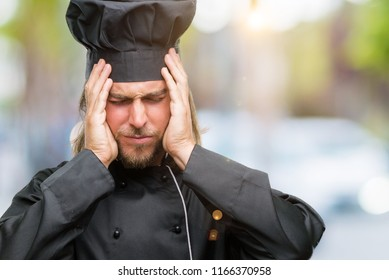 Young handsome cook man with long hair over isolated background suffering from headache desperate and stressed because pain and migraine. Hands on head.