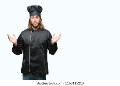Young handsome cook man with long hair over isolated background clueless and confused expression with arms and hands raised. Doubt concept.