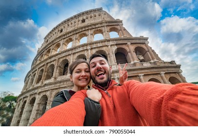 Young handsome couple at the Colosseum, Rome - Happy tourists visiting italian famous landmarks and taking photo selfie portrait