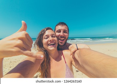 Young handsome couple making selfie photo at the beach in Australia