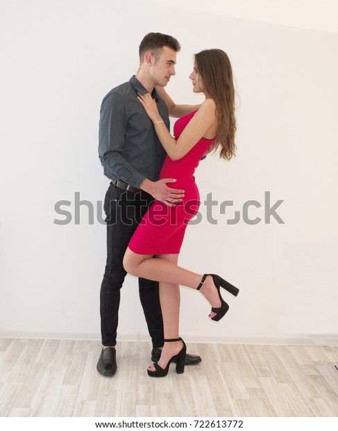 Young, handsome couple posing together on white, isolated background.