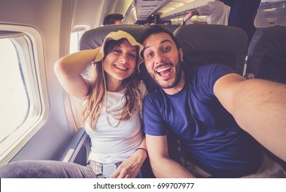 Young handsome couple taking a selfie on the airplane during flight around the world. They are a man and a woman, smiling and looking at camera. Travel, happiness and lifestyle concepts.