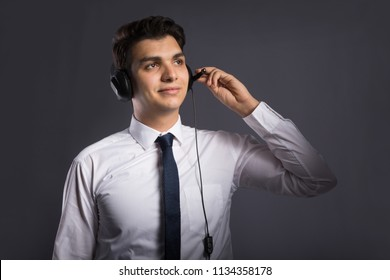 young handsome customer service standing in formal outfit wearing headset seems that he is speaking with a customer , on dark grey background