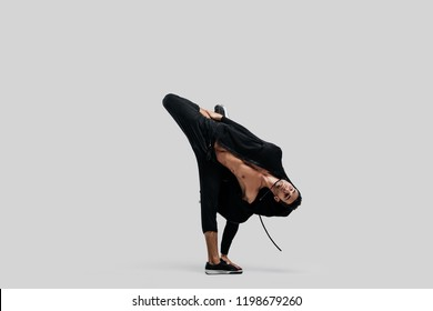 Young handsome young dancer dressed in black pants, a sweatshirt on a naked torso dances  breakdance holding one hand and one foot on the floor