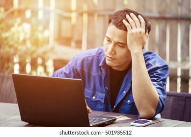 Young handsome dark-haired businessman in casual clothes using laptop and having headache while working in coffee shop