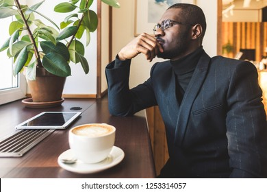 Young handsome dark-skinned businessman drinks coffee in a cafe.