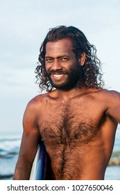 A young handsome dark-skinned man with a surfboard