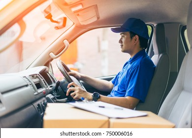 Young handsome delivery man driving his van with packages on the front seat