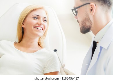 Young handsome dentist talks with happy woman patient sitting on dentist chair in dental clinic. Dentistry care concept.