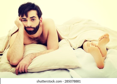 Young handsome depressed man in bed.