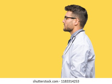 Young handsome doctor man over isolated background looking to side, relax profile pose with natural face with confident smile.