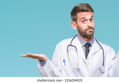 Young handsome doctor man over isolated background clueless and confused expression with arms and hands raised. Doubt concept.