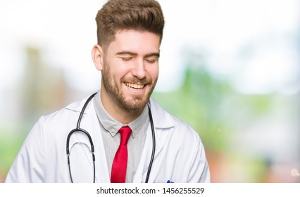 Young handsome doctor man wearing medical coat Smiling and laughing hard out loud because funny crazy joke. Happy expression.