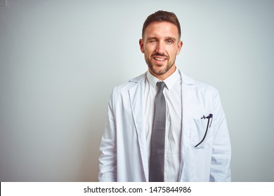 Young handsome doctor man wearing white profressional coat over isolated background winking looking at the camera with sexy expression, cheerful and happy face.