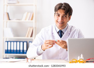 Young handsome doctor oculist working at the clinic