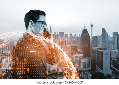 A young handsome eastern businessman processing conference call to develop social media marketing strategy to achieve business goals. Hologram icons over Kuala Lumpur background.