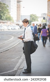 young handsome elegant blonde model man using tablet technological device in the city
