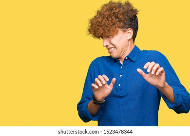 Young handsome elegant man with afro hair disgusted expression, displeased and fearful doing disgust face because aversion reaction. With hands raised. Annoying concept.