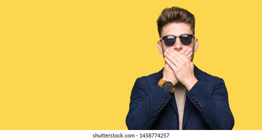 Young handsome elegant man wearing sunglasses shocked covering mouth with hands for mistake. Secret concept.