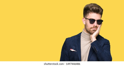 Young handsome elegant man wearing sunglasses thinking looking tired and bored with depression problems with crossed arms.