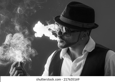 Young handsome elegant stylish male model wearing sunglasses and hat smoking a cigarette black and white portrait