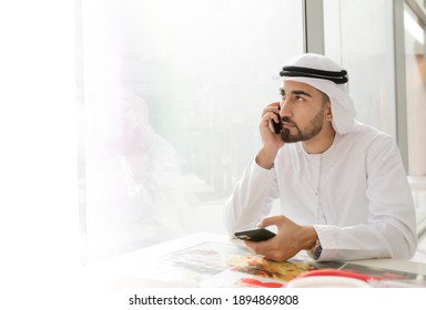 Young handsome Emirati business man in UAE traditional outfit talking on mobile phone. Arabic ambitious mature businessman.