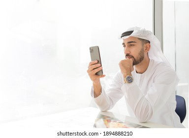 Young handsome Emirati business man in UAE traditional outfit looking at mobile phone. Arabic ambitious mature businessman.
