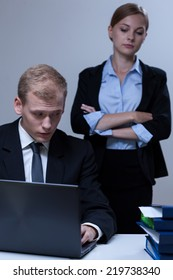 Young handsome employee looking at his attractive female boss